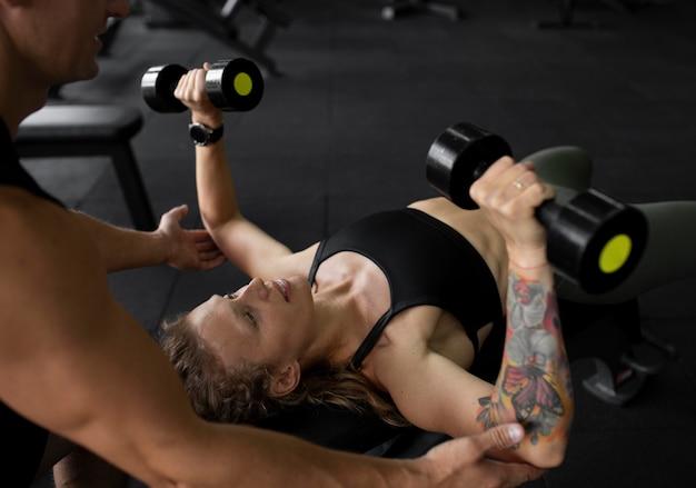 Close-up mulher treinando com halteres