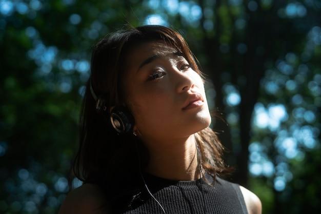 Close-up, mulher usando fones de ouvido do lado de fora