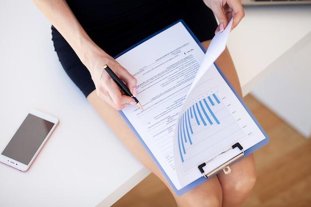 Close-up mulher verifica gráficos de receita da empresa.