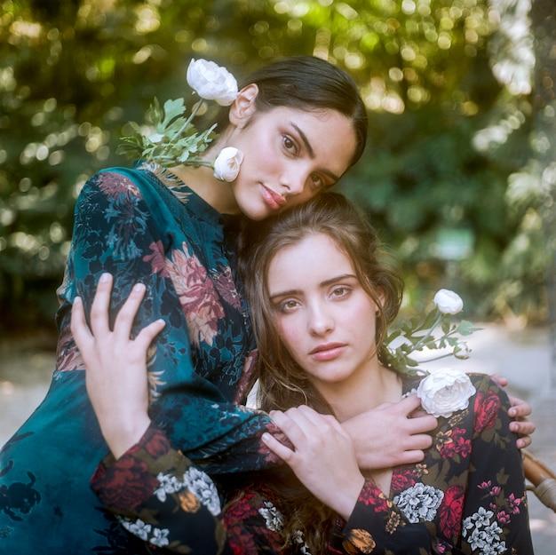 Close-up, mulheres, em, vestidos florais, segurando, um ao outro