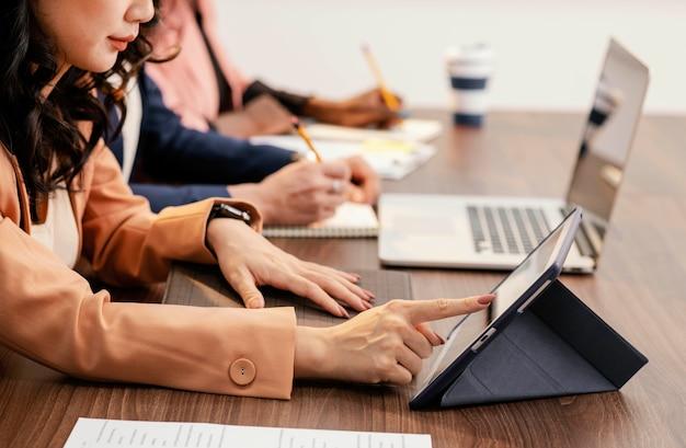 Close-up mulheres trabalhando com dispositivos