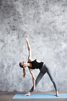 Close-up na aptidão da mulher de ioga no tapete no ginásio