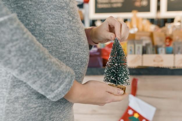Close-up na barriga de uma mulher grávida com uma pequena árvore de natal