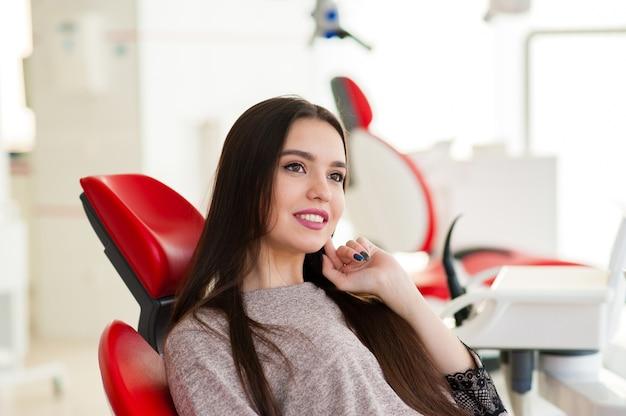 Close-up na bela mulher na cadeira odontológica