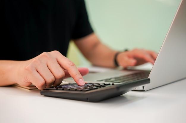 Close-up na imprensa de dedo de homem empregado na calculadora para gerenciar as despesas conceito