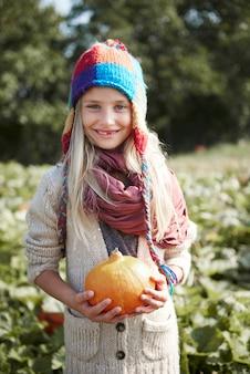 Close-up na jovem e feliz garota com abóbora