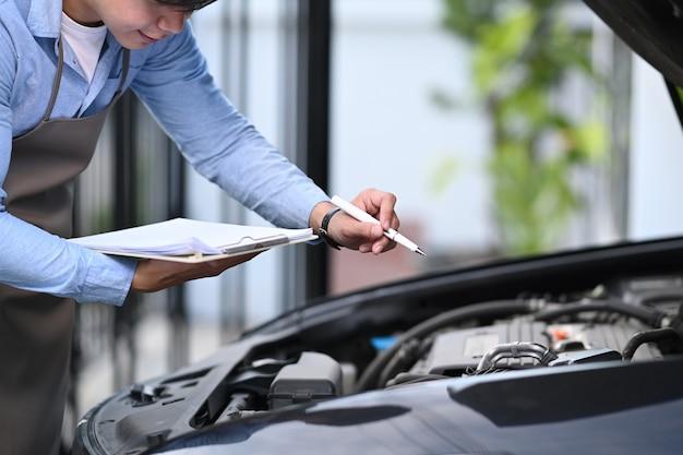 Close-up na lista de verificação técnica consertar máquina um carro