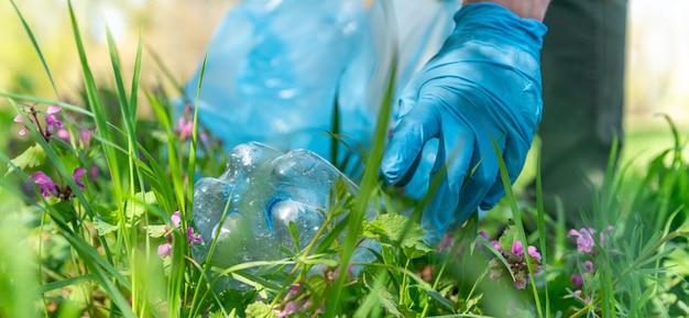 Close-up na mão de um homem em luvas de borracha, coleta de resíduos plásticos na natureza