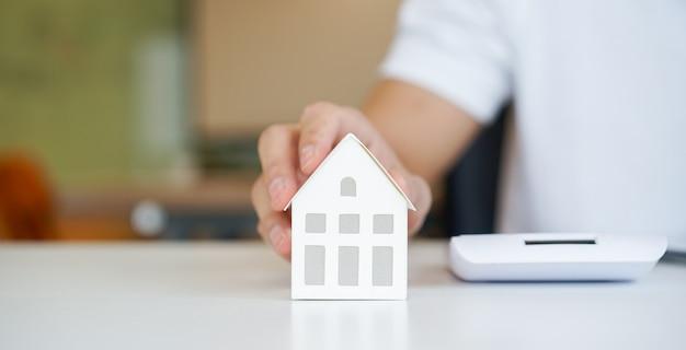 Close-up na mão do homem tocando o modelo de casa em cima da mesa para hipoteca de empréstimo e refinanciar o plano