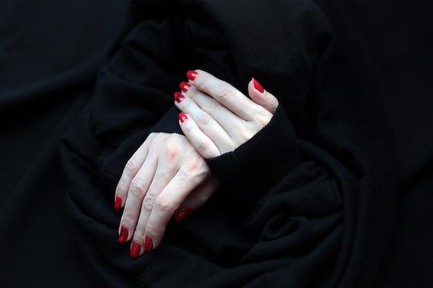 Close-up na mão feminina bonita com manicure vermelha bonita com um fundo preto. unhas vermelhas em uma superfície preta