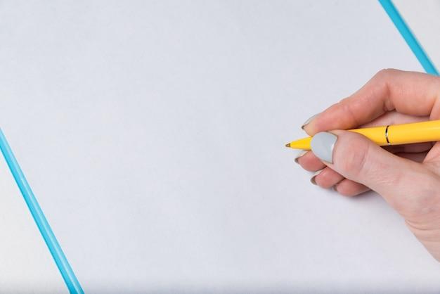 Close-up na mão feminina com caneta em uma folha de papel em branco