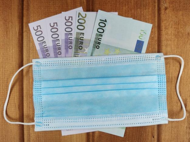 Close-up na máscara médica com notas de euro