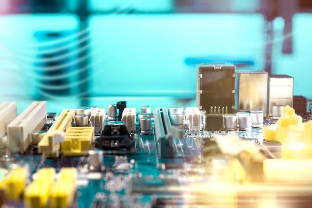Close up na placa eletrônica na oficina de reparações de hardware, na imagem borrada e tonificada. dof raso, sem ponto focal.
