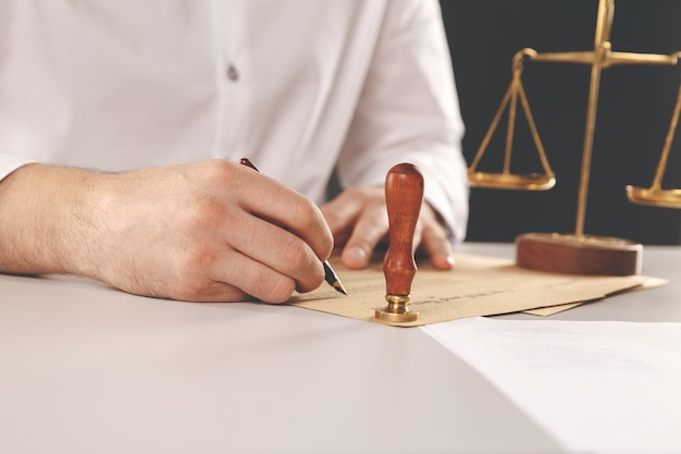 Close-up na tinta de mão pública de tabelião homem carimbando o documento. conceito de notário público