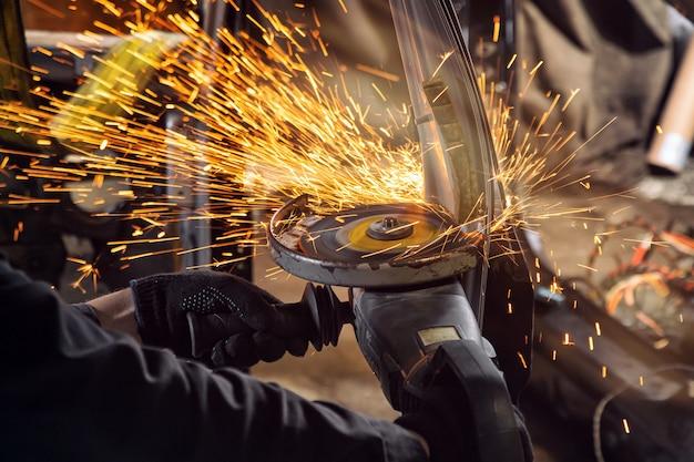 Close-up nas laterais solta faíscas brilhantes da retificadora. um jovem soldador masculino em luvas de trabalho mói um carro velho com rebarbadora na garagem