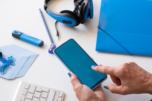 Close-up nas mãos da mulher usando um telefone inteligente com display azul. cor azul nos acessórios