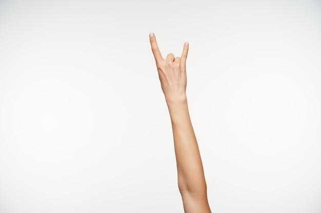 Close-up nas mãos de uma mulher atraente mostrando os dedos em um gesto de metal e rocha