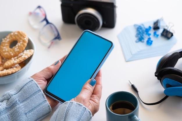 Close-up nas mãos de uma mulher segurando um telefone inteligente com display azul. cor azul nos acessórios