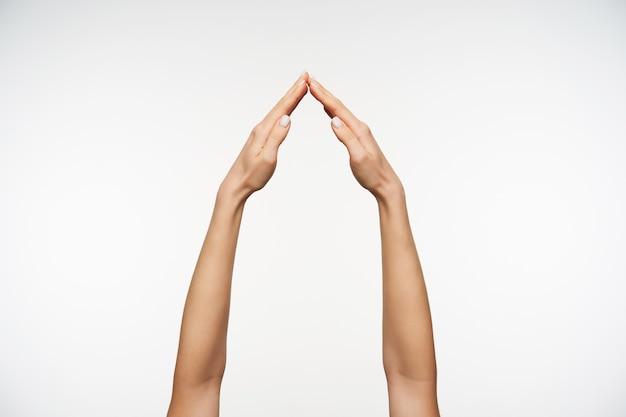 Close-up nas mãos de uma mulher sendo levantadas enquanto imita o sinal de casa
