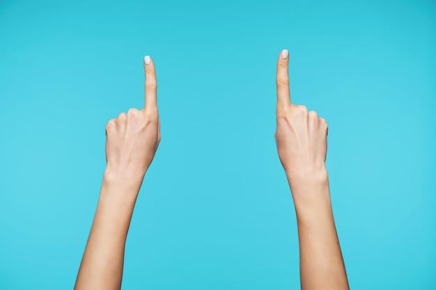 Close-up nas mãos levantadas de uma jovem com manicure branca isolada