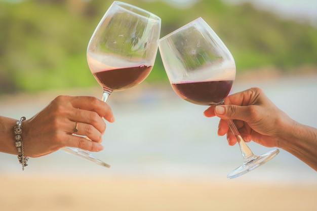 Close-up nas mãos segurando copos de vinho tinto na praia, conceito de celebração