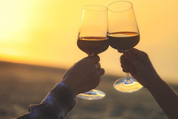Close-up nas mãos segurando copos de vinho tinto na praia durante o pôr do sol, conceito de celebração