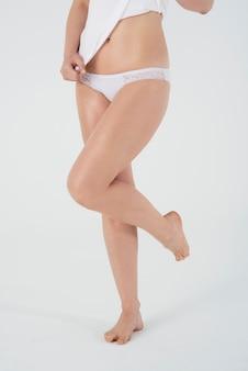 Close-up nas pernas da mulher em roupas íntimas básicas isoladas