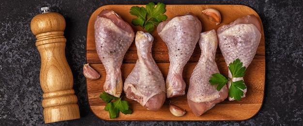 Close-up nas pernas de frango cru na tábua