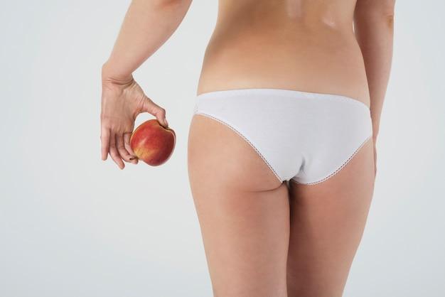 Close-up nas pernas de uma mulher em roupas íntimas básicas isoladas