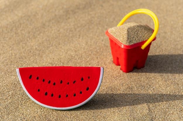 Close-up no balde do castelo de areia na areia com um brinquedo de melancia