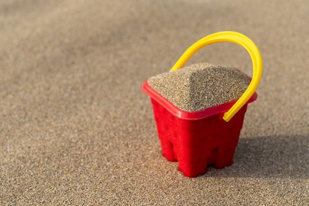 Close-up no balde do castelo de areia na areia