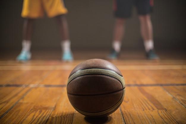 Close-up no basquete, colocando no chão na frente dos jogadores de basquete