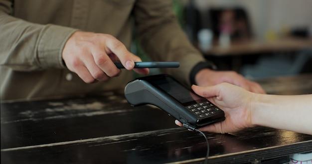 Close-up no café mulher faz café para viagem para um cliente que paga por telefone celular sem contato para sistema de cartão de crédito.