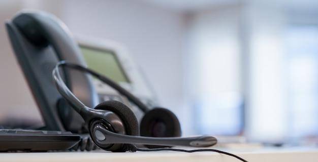 Close-up no centro de chamada de fone de ouvido com telefone no conceito de sala de operação de monitoramento de escritório