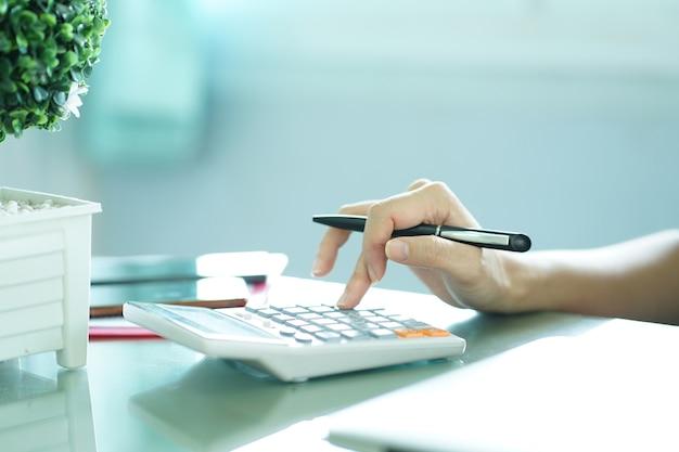 Close-up no dedo mão pressione na calculadora para computação