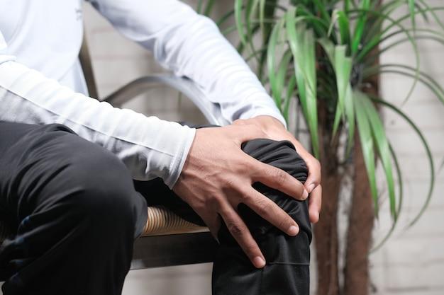 Close-up no homem que sofre de dor nas articulações do joelho.
