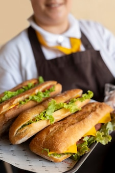 Close-up no jovem chef segurando sanduíches