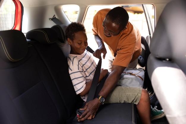 Close-up no pai protegendo o cinto de segurança do filho