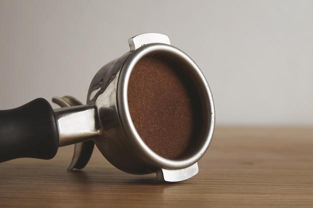 Close-up no porta-filtro de aço com pó de café moído pressionado para dentro. isolado na mesa de madeira em uma loja de café. preparação profissional de café