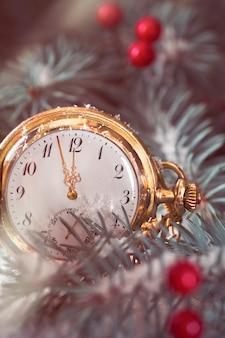 Close-up no relógio de bolso antigo mostrando cinco a doze entre as decorações de inverno