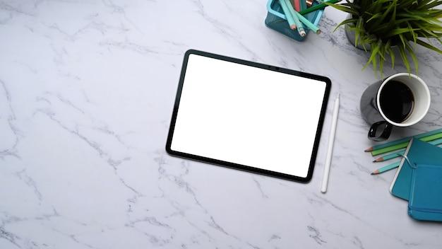 Close-up no tablet digital com tela branca, caneta stylus, xícara de café e artigos de papelaria