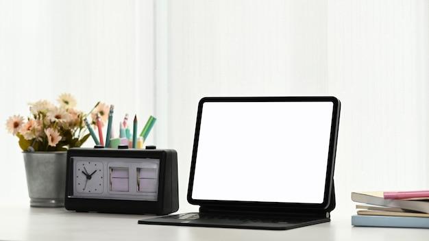 Close-up no tablet, relógio, planta e caderno na mesa branca