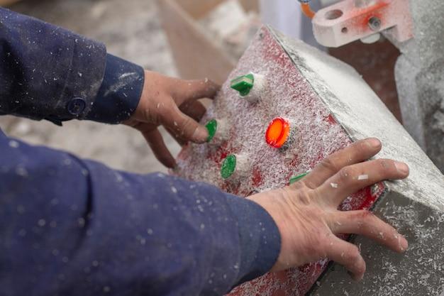 Close-up no trabalhador usando o botão de controle na fábrica