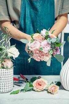 Close-up no trabalho criativo florista. a fêmea que arranja um ramalhete com flores usa as ferramentas do florista que estão pelo local de trabalho na loja. entrega de flores. copie o espaço. local de trabalho e conceito profissional