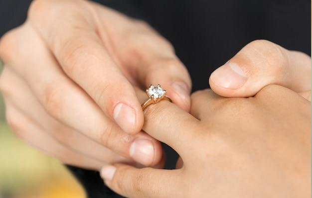 Close-up noivo colocando a aliança de casamento na noiva