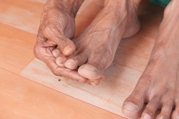 Close-up nos pés das mulheres sênior e massagem de mãos no local da lesão.