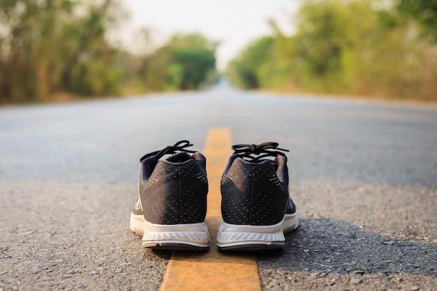 Close-up novos tênis pretos na estrada de asfalto em tempo de manhã