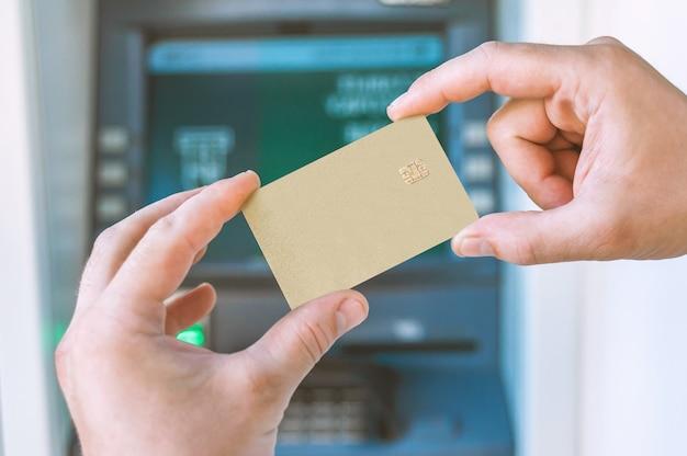 Close-up, o cara tem na mão um cartão do banco na frente do caixa eletrônico.