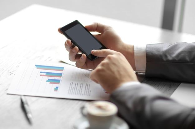 Close up. o empresário usa seu smartphone para verificar dados financeiros. conceito de negócio