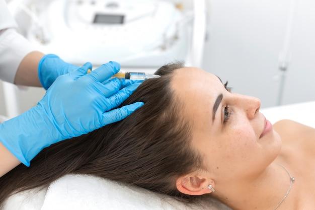 Close-up, o esteticista faz injeções de vitaminas no couro cabeludo para fortalecer os cabelos